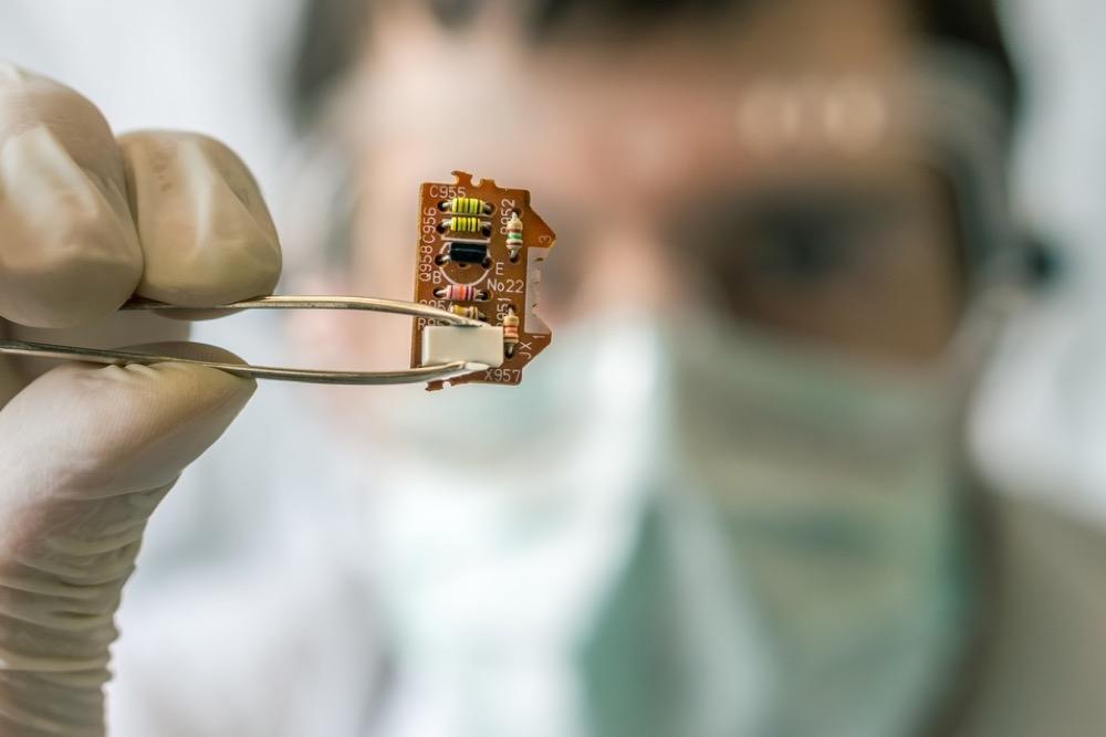 電子チップをピンセットでつまむ研究員