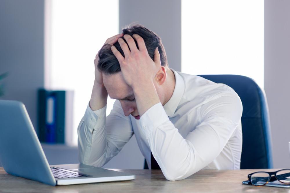 オフィスの机に肘をついて頭を抱える男性