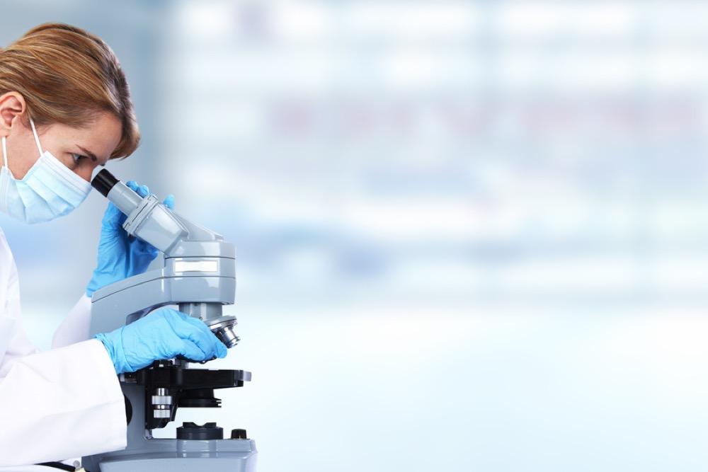顕微鏡をのぞく女性研究員