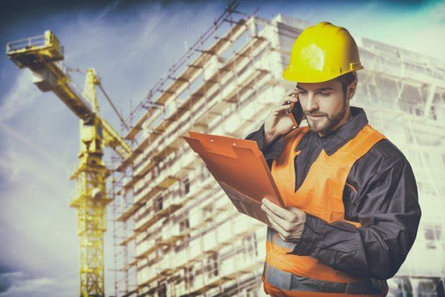 建設中のビルの前で電話をする施工管理士