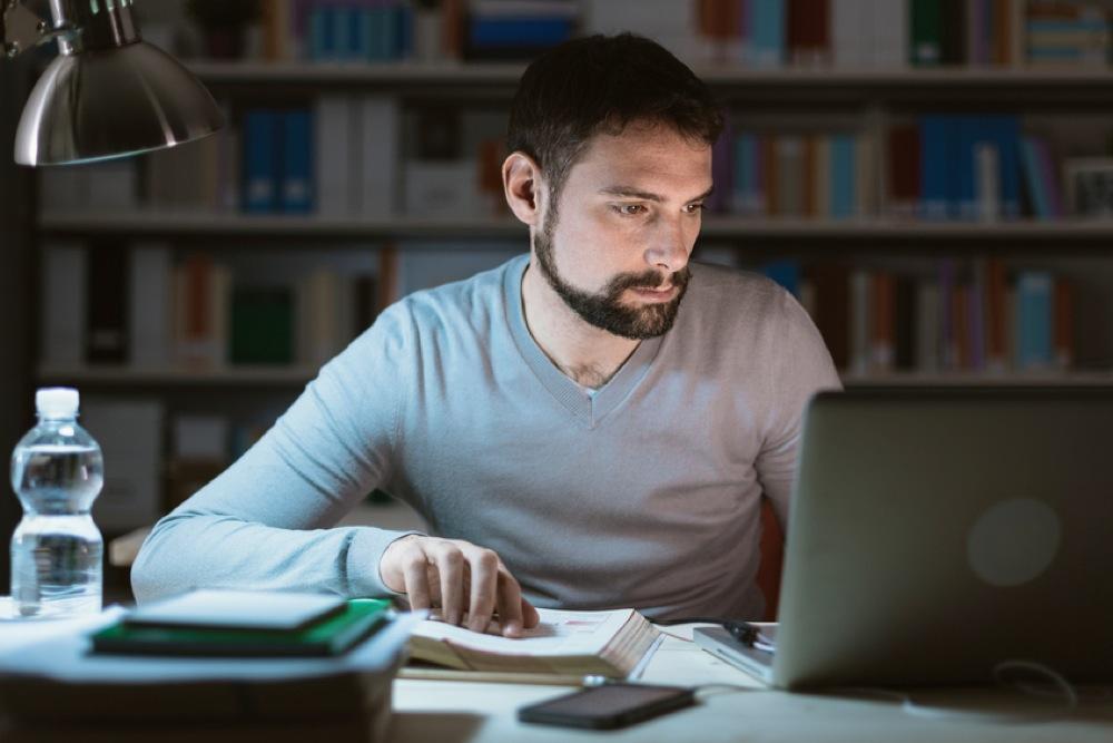 深夜の暗い部屋で仕事をする男性