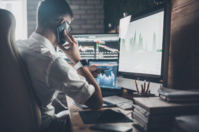 薄暗いオフィスで仕事をしながら電話をかける男性