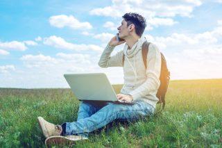 青空が広がる草原に座り、スマートフォンで通話する男性