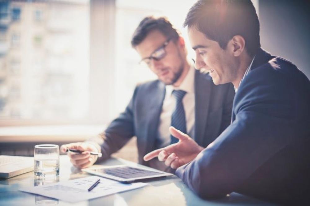 笑顔で仕事の会話をするスーツ姿の男性2人