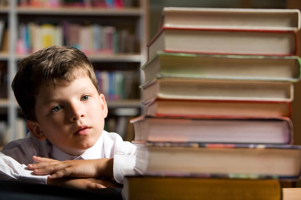 積み上げられた本をぼんやり見つめる少年