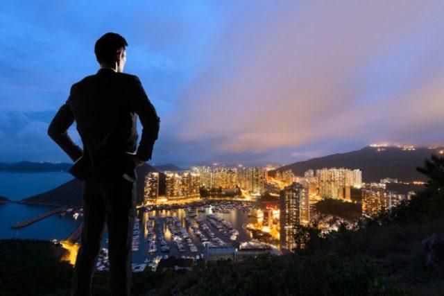 高台から夜景を見つめるスーツ姿の男性