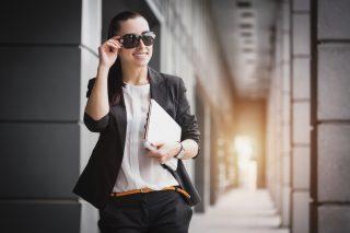 サングラスをかけて颯爽と歩くスーツを着た女性