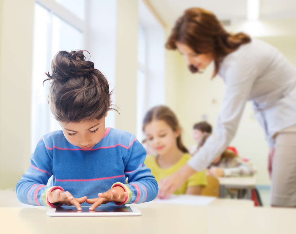 教室の中でタブレット端末を操作する子供達と教師