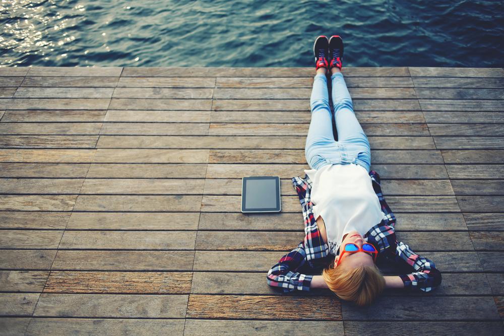 海辺の桟橋に寝転びながらリラックスする女性