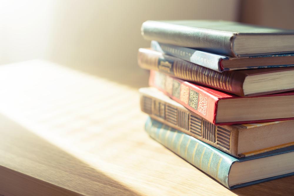 机の上に重ねて置かれたたくさんの本
