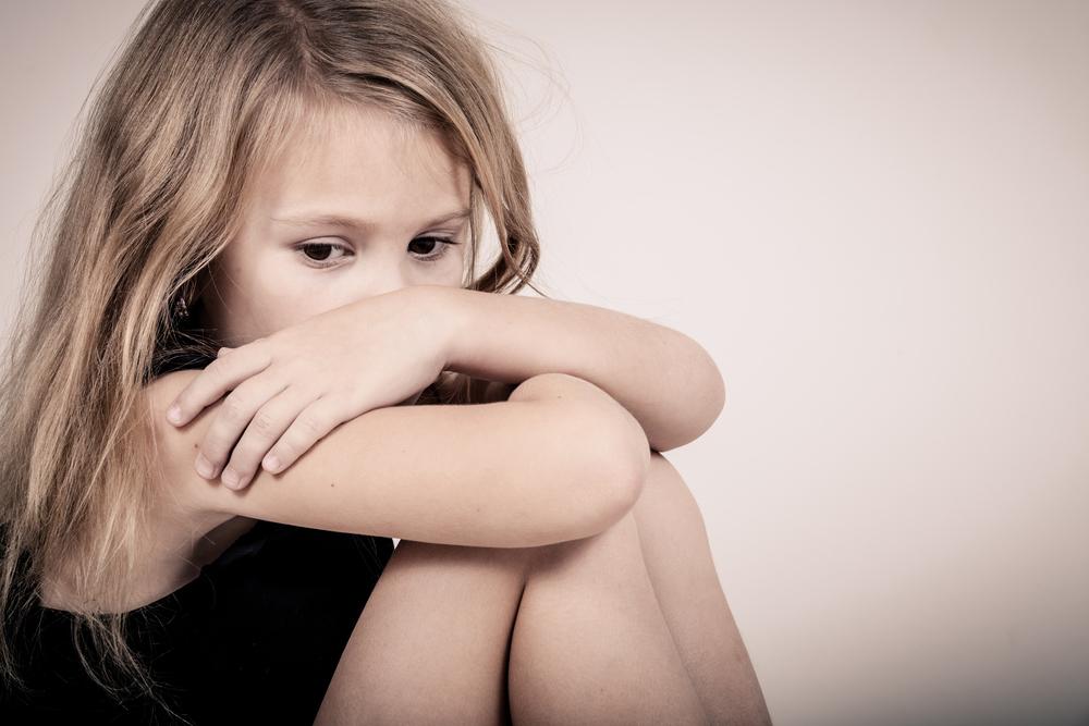膝を抱えて不安そうな表情で座り込む少女