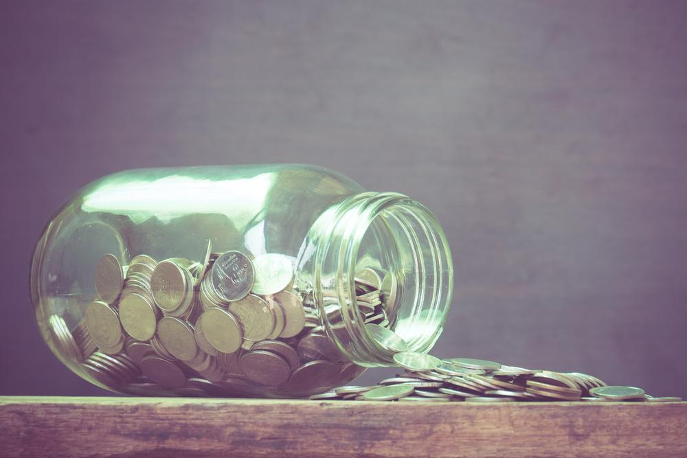 横倒しになった瓶から溢れる大量のコイン