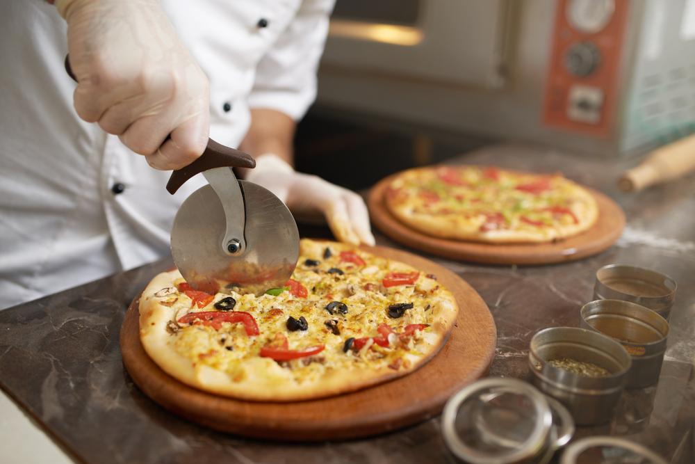 ピザをカットする調理師