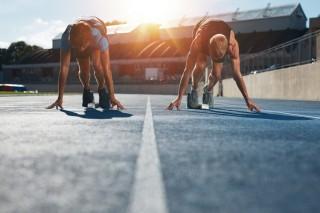 スタートラインにつき、走ろうとする陸上選手