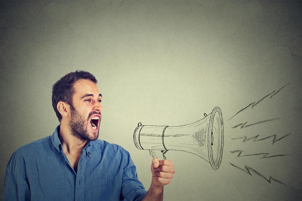 拡声器を使って話す男性