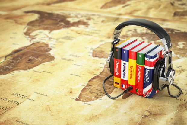 多言語の書籍を挟むヘッドフォン