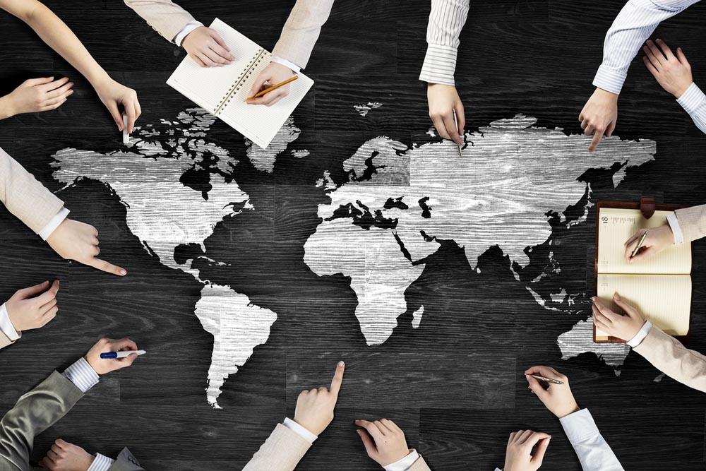 世界地図を見ながら話し合う人々