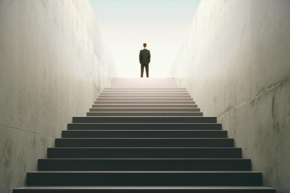 長い階段を登りきったスーツを着た男性