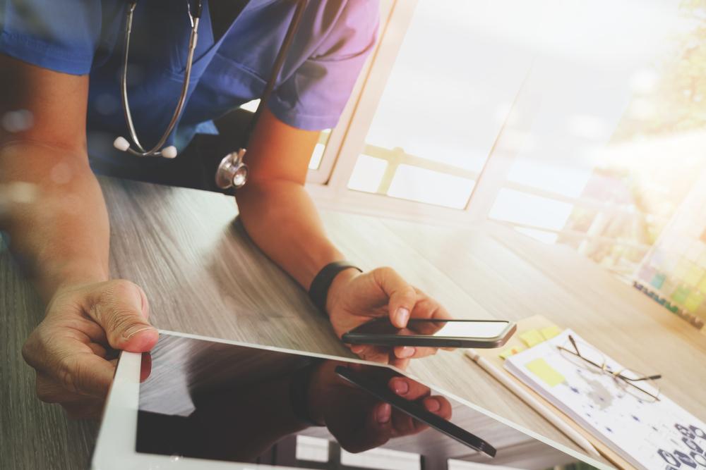 タブレット端末やスマートフォンを使って仕事をする医療関係者