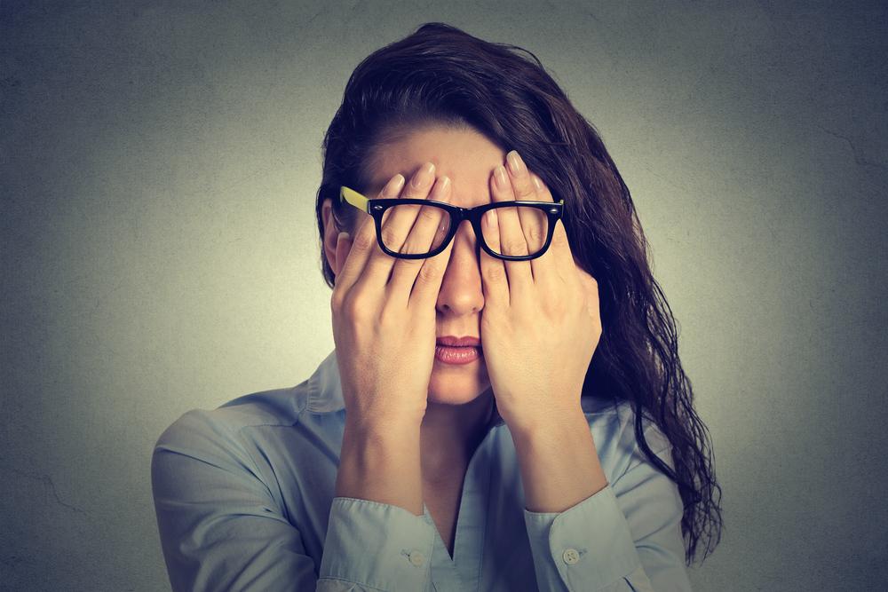 両手で顔を覆うメガネをかけた女性