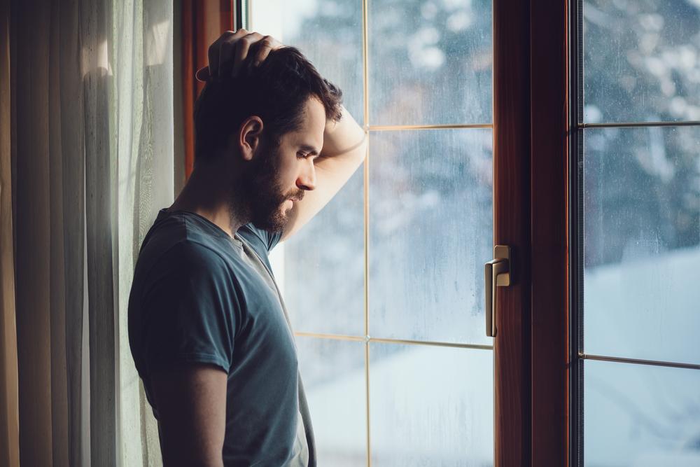 雨粒のついた窓際に立ち俯く男性