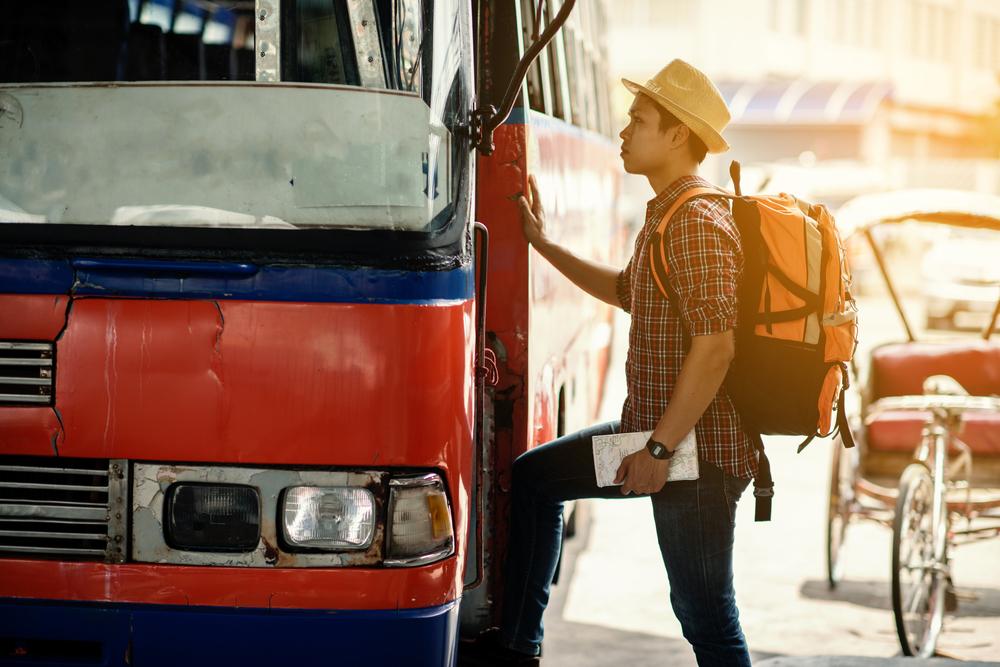 大きなバックパックを背負ってバスに乗り込む男性