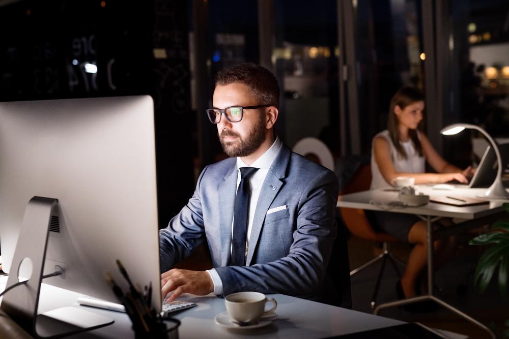 夜の暗いオフィスで残業するスーツの男性