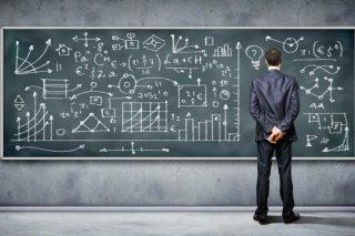 黒板に書かれた数値を読み解く男性