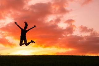 夕日をバックに飛び上がって喜ぶ女性のシルエット