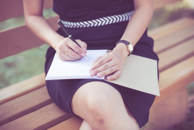 公園のベンチに座ってメモ帳にポイントを書き出す女性