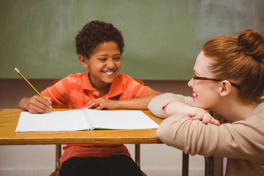 勉強をする子供とそれを見る教師の女性