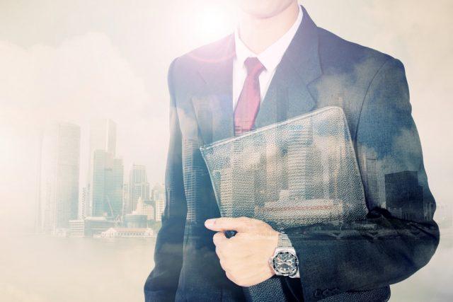 ファイルを持つ男性とビジネス街の風景