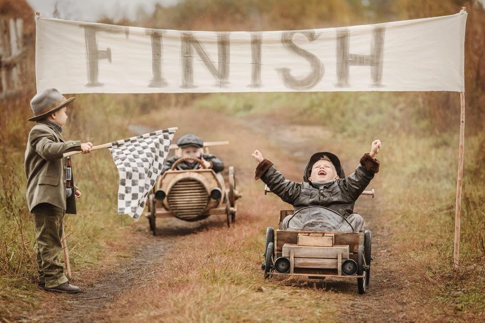 おもちゃの車でレースにゴールした子供