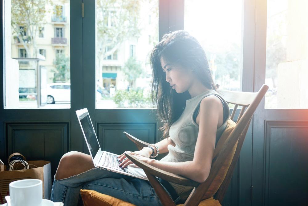 カフェの窓際に座って仕事をする女性