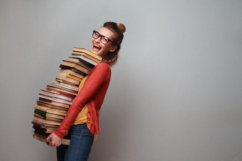 たくさんの本を抱えた笑顔の女性