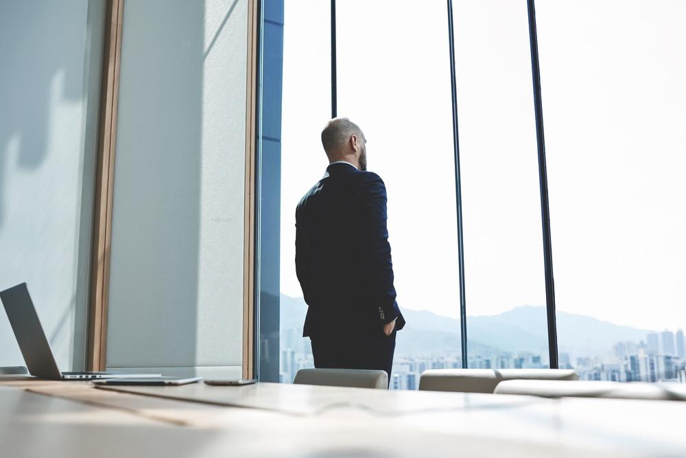 オフィスの窓から外を見つめるスーツを着た男性