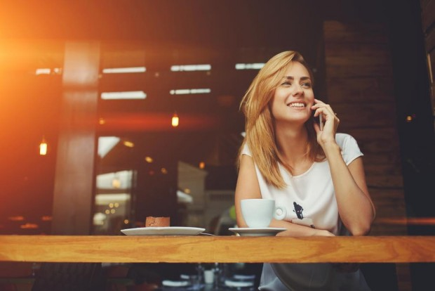 カフェでお茶をしながら笑顔で通話する女性