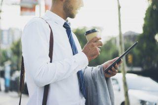 テイクアウトのコーヒーを飲みながらタブレット端末を見るサラリーマン