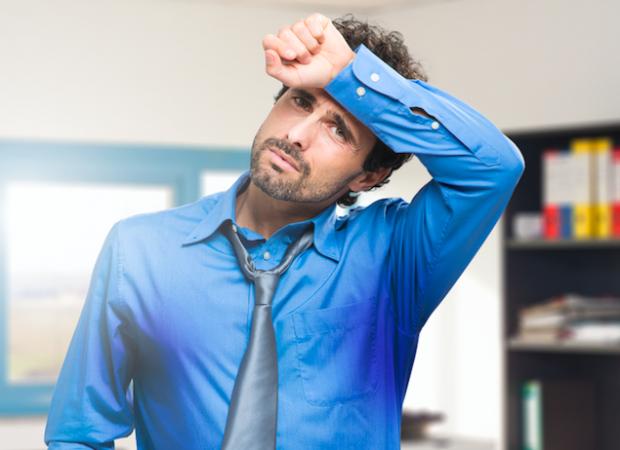 困った表情をする青いシャツを着た男性