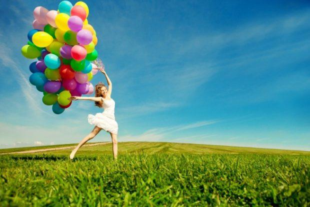 たくさんのカラフルな風船を持つ女性