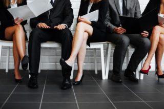 椅子に座って書類を読むスーツ姿の男女