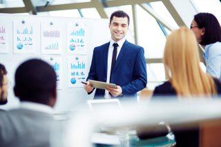 会議中に笑顔でプレゼンする男性