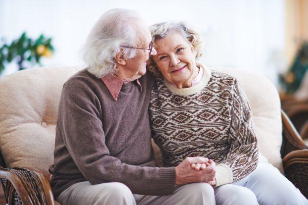 手を繋いでソファーに座る老夫婦