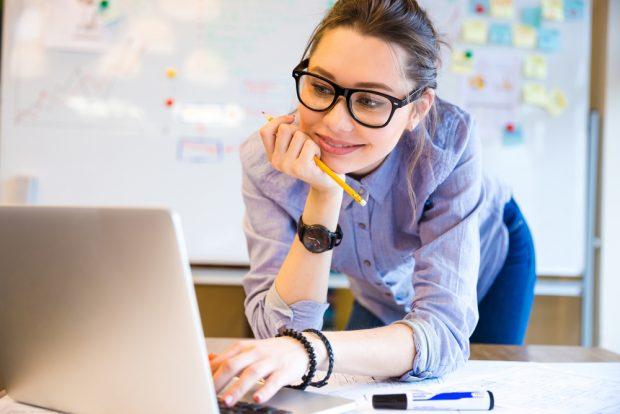 笑顔でノートパソコンを見る黒縁メガネをかけた女性