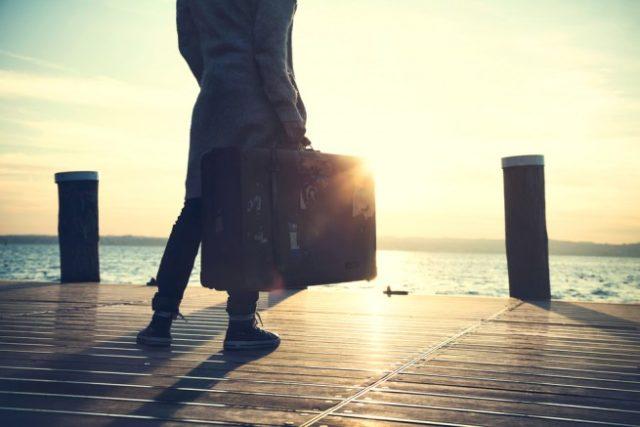 スーツケースを持地、波止場で海を見つめる人