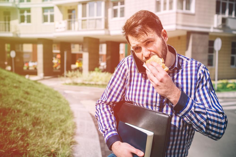 サンドイッチをかじりながら忙しそうに仕事へ向かう男性