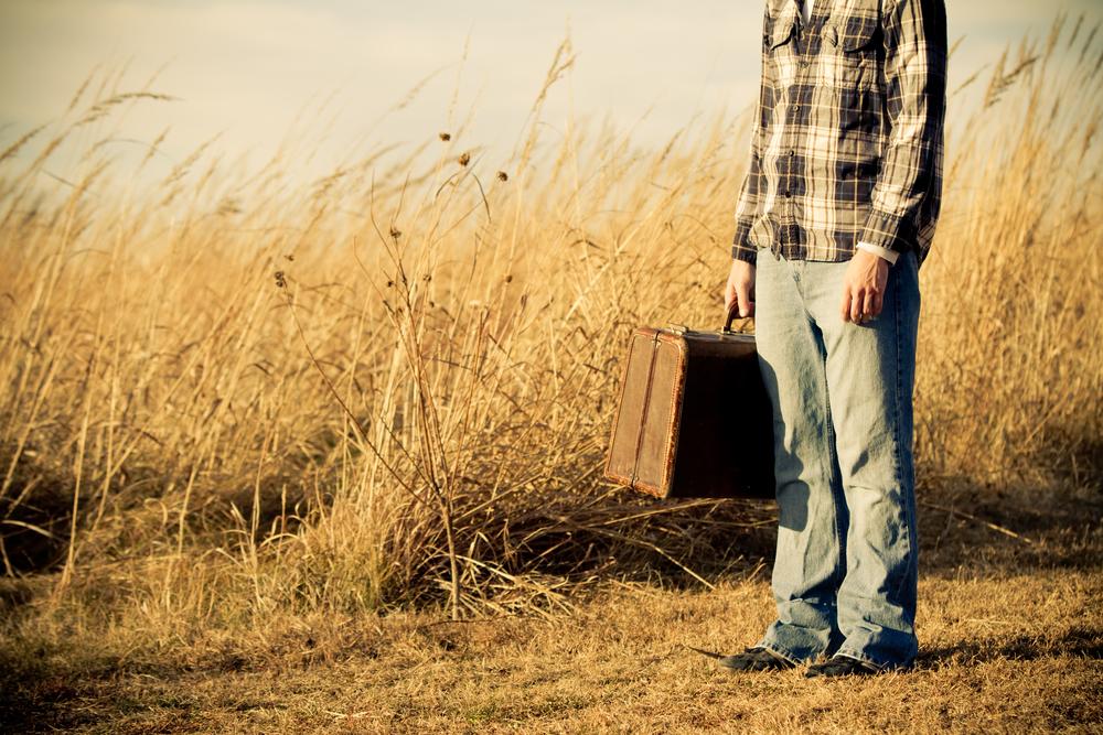 荒れた草原に呆然と立ち尽くす、古びたスーツケースを持った男性
