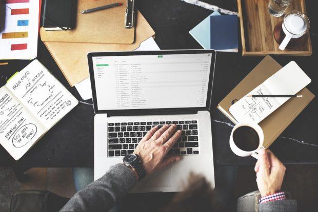ノートパソコンでメールを確認する男性