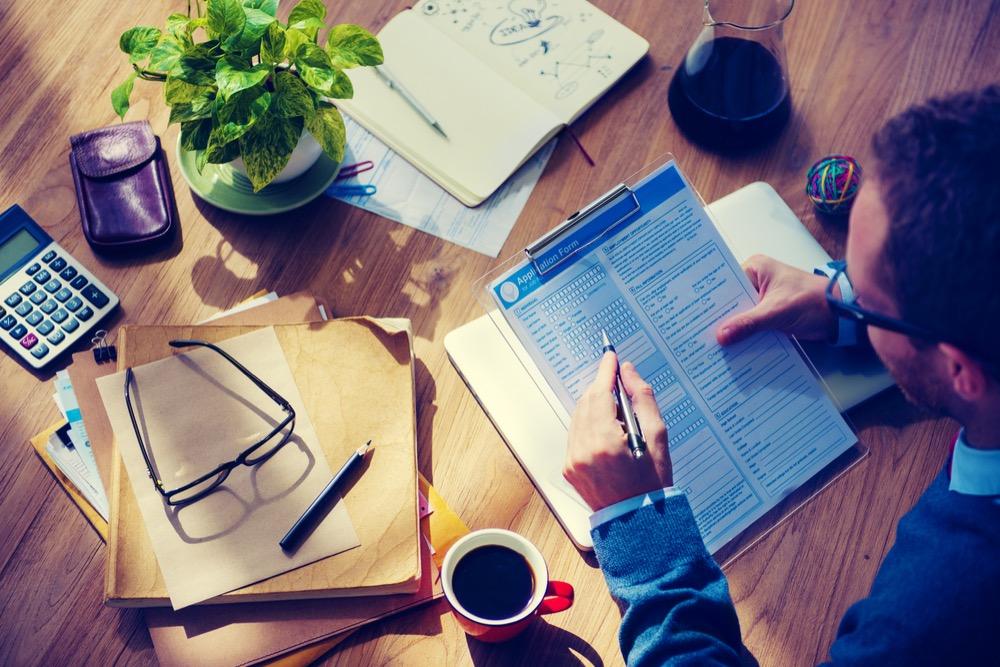木製のテーブル上の応募用紙を見る男性