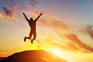朝日を受けながら飛び上がる男性のシルエット